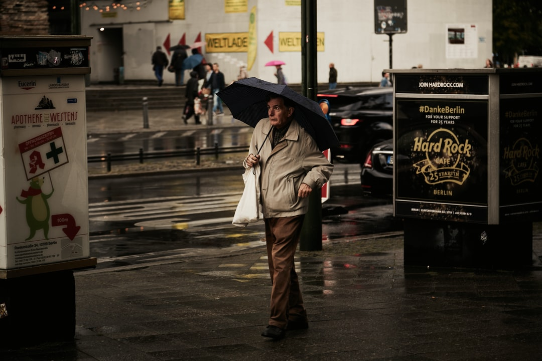 Old Man Holing A Plastic Bag Under the Umbrella In A Wet Warm Street of Berlin. - unsplash