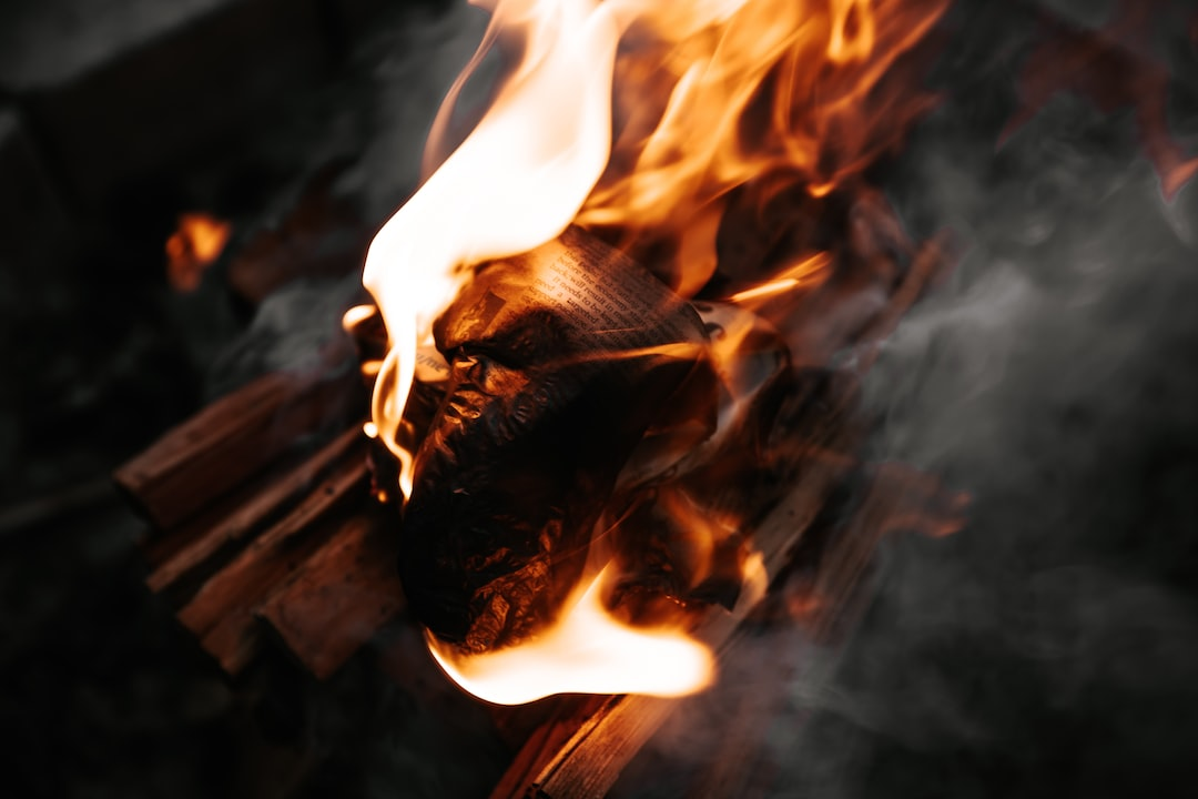 A Scrap of Newspaper Sitting In the Fire, With the Words Being Slowlyt Eaten By the Flames. - unsplash