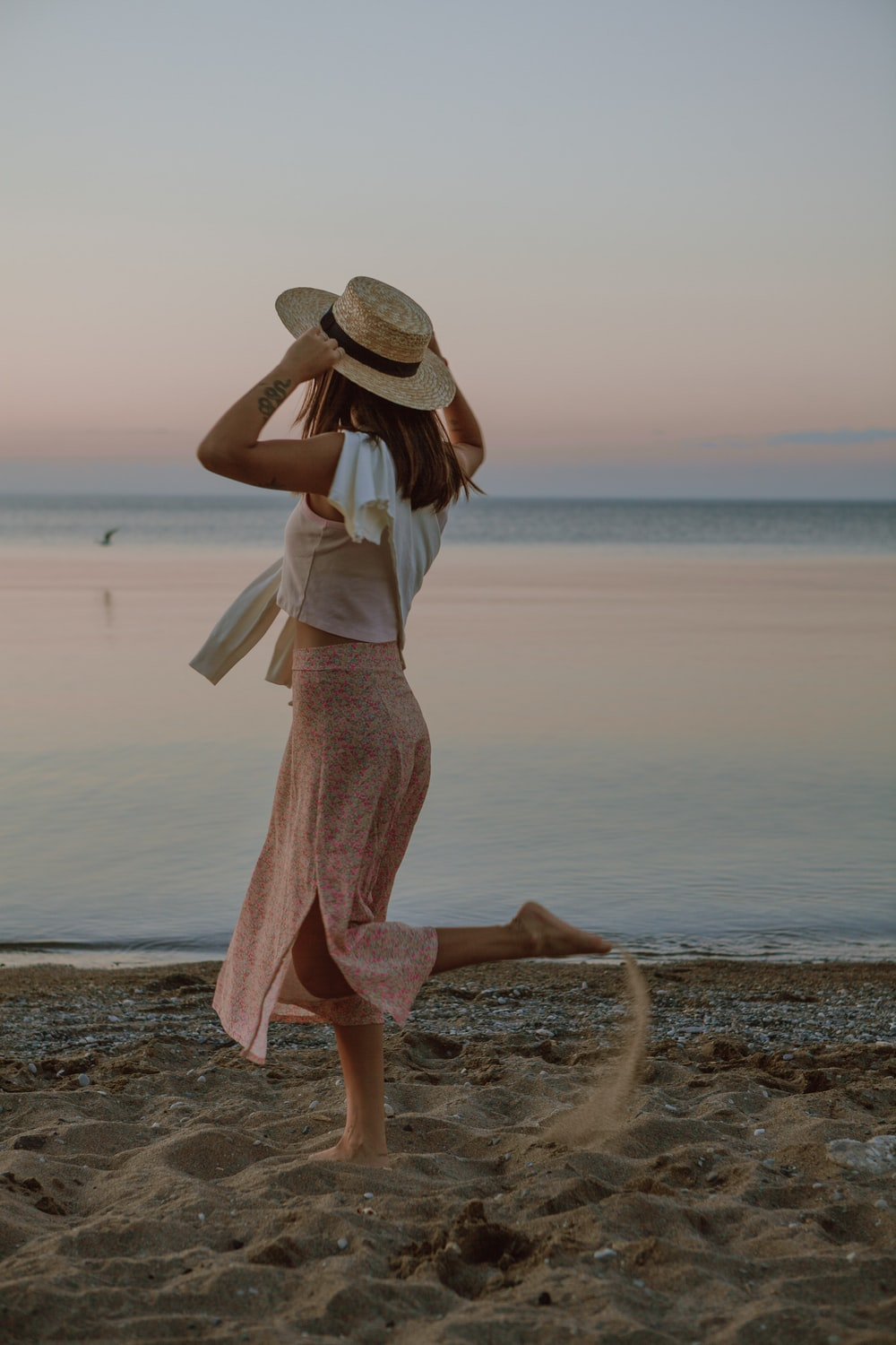 woman in white dress and brown hat standing on seashore during daytime