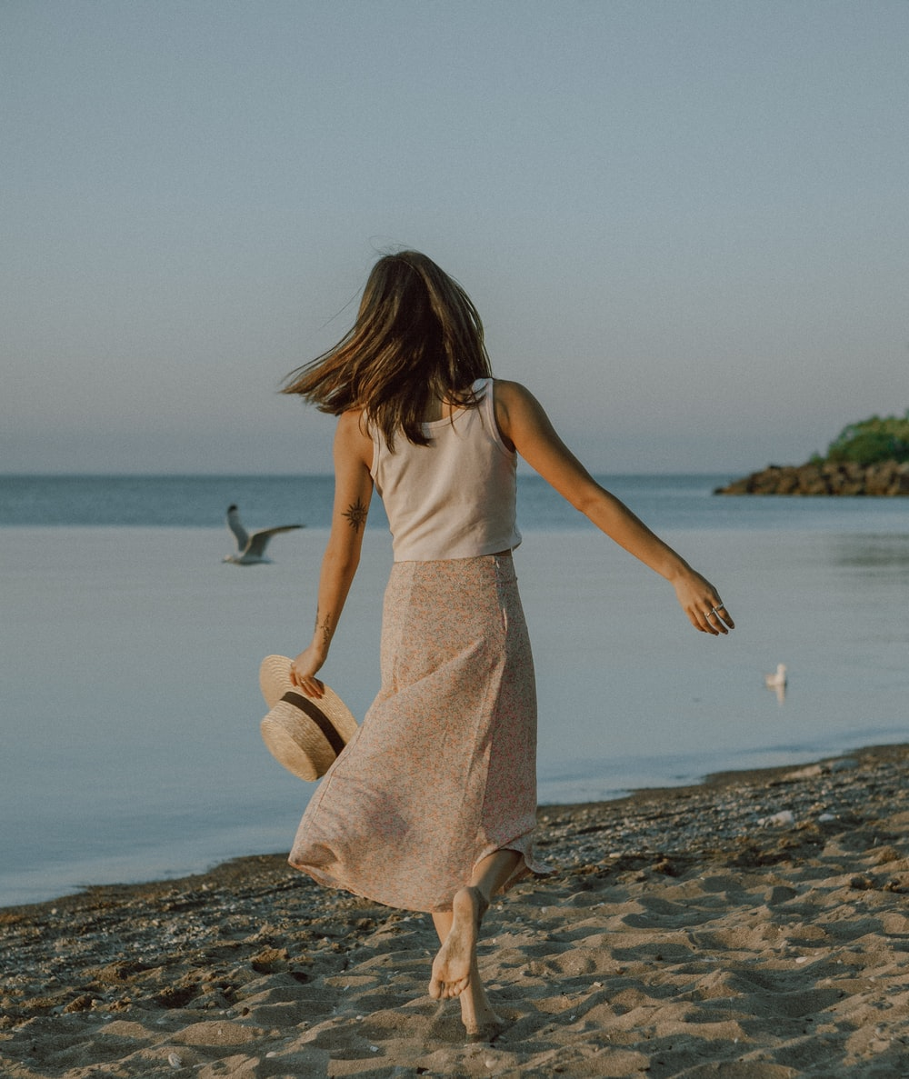 woman in white tank dress standing on beach shore during daytime