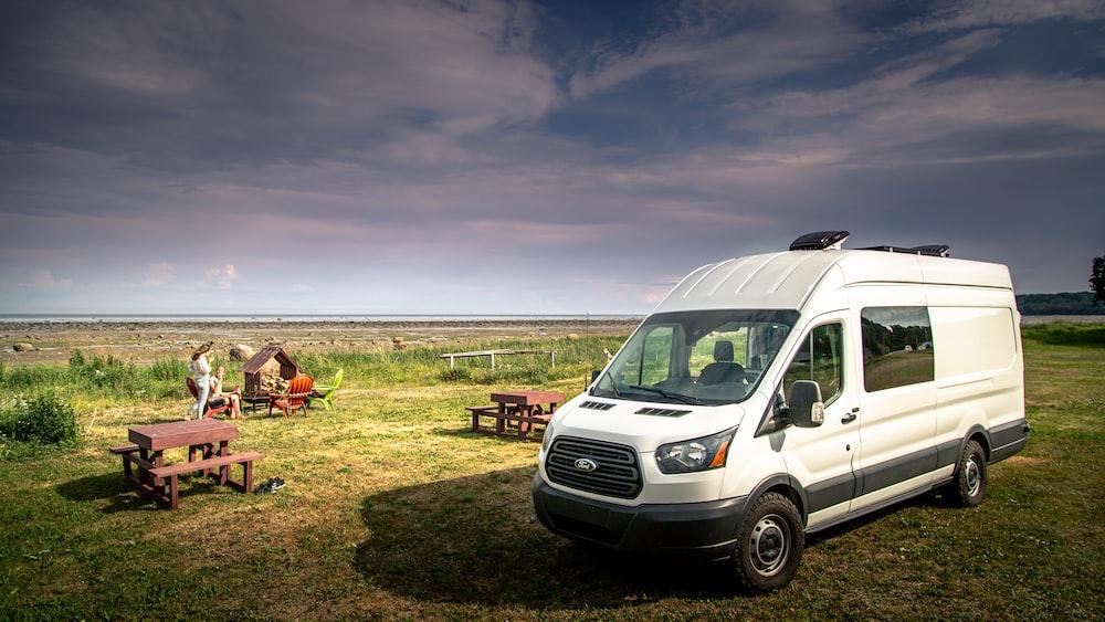 white van on green grass field during daytime