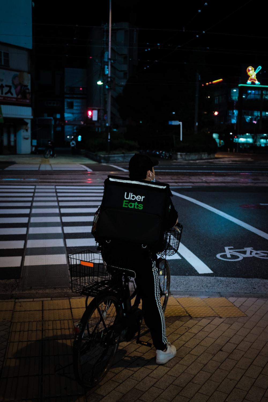 woman in black jacket riding bicycle on pedestrian lane during night time