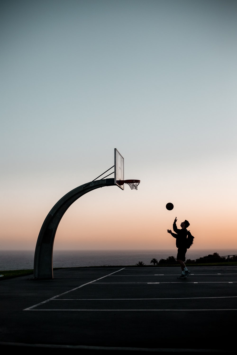 man in black jacket and pants playing basketball during sunset