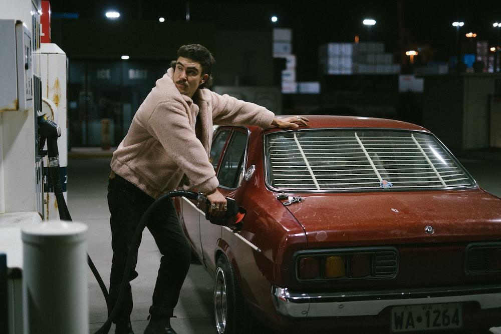 man in gray hoodie standing beside red car