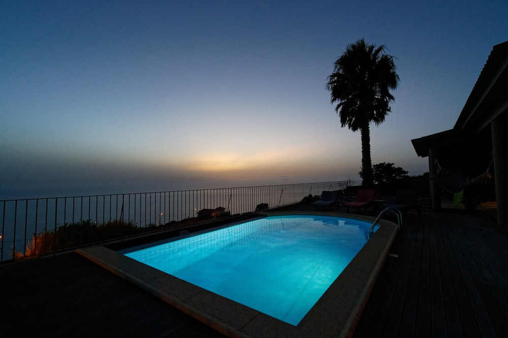 swimming pool near palm trees during sunset