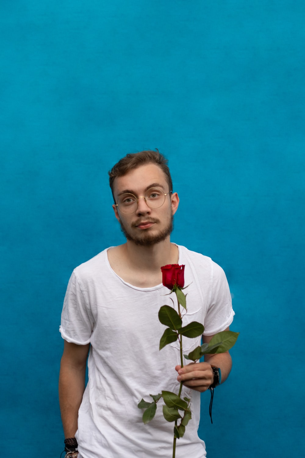 man in white crew neck t-shirt holding red rose