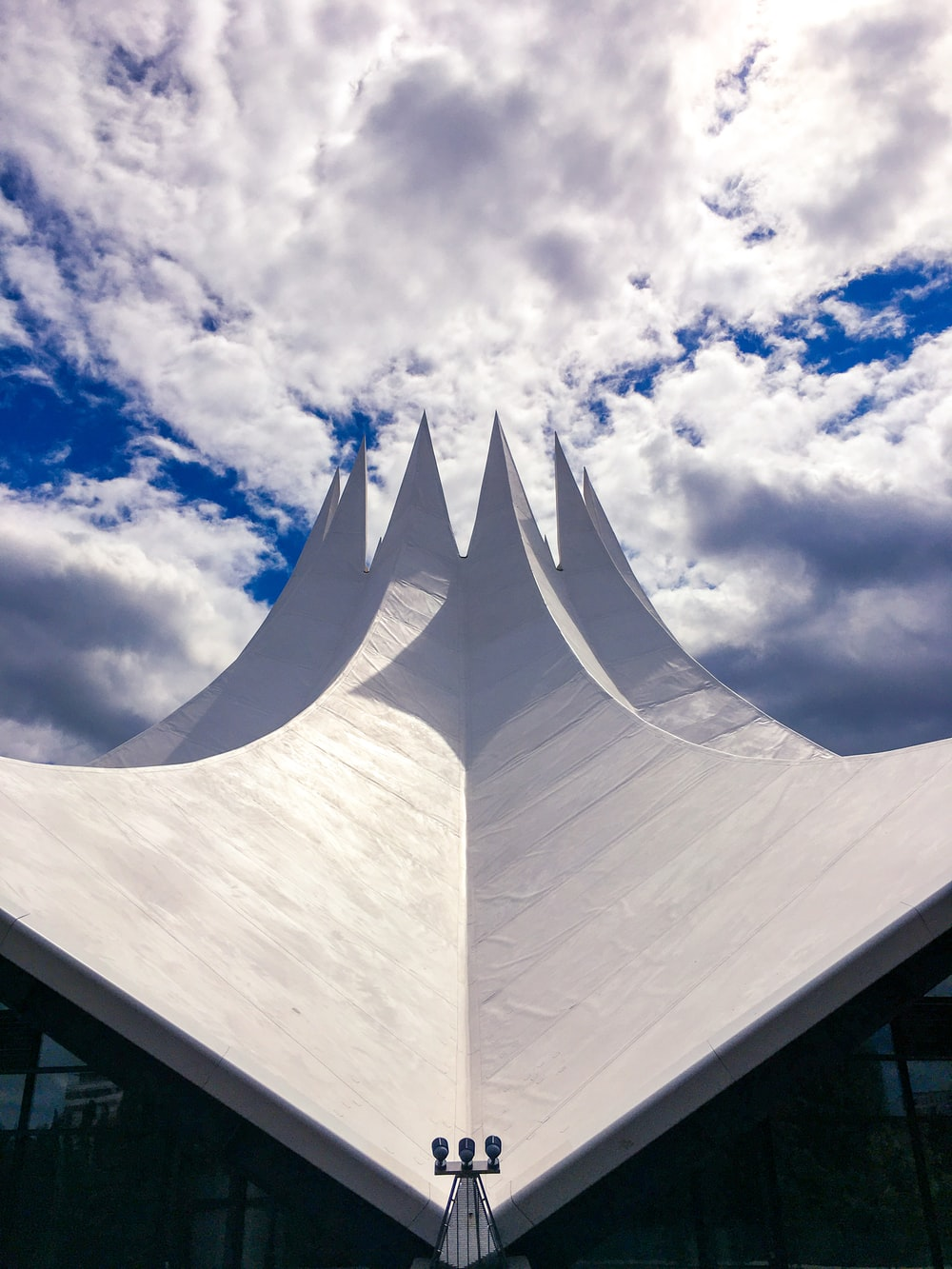 white concrete building under white clouds and blue sky during daytime