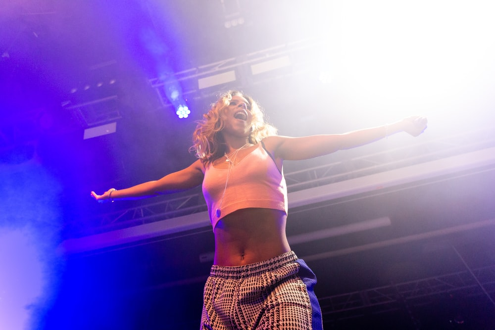 woman in white sports bra and black and white plaid skirt standing on stage