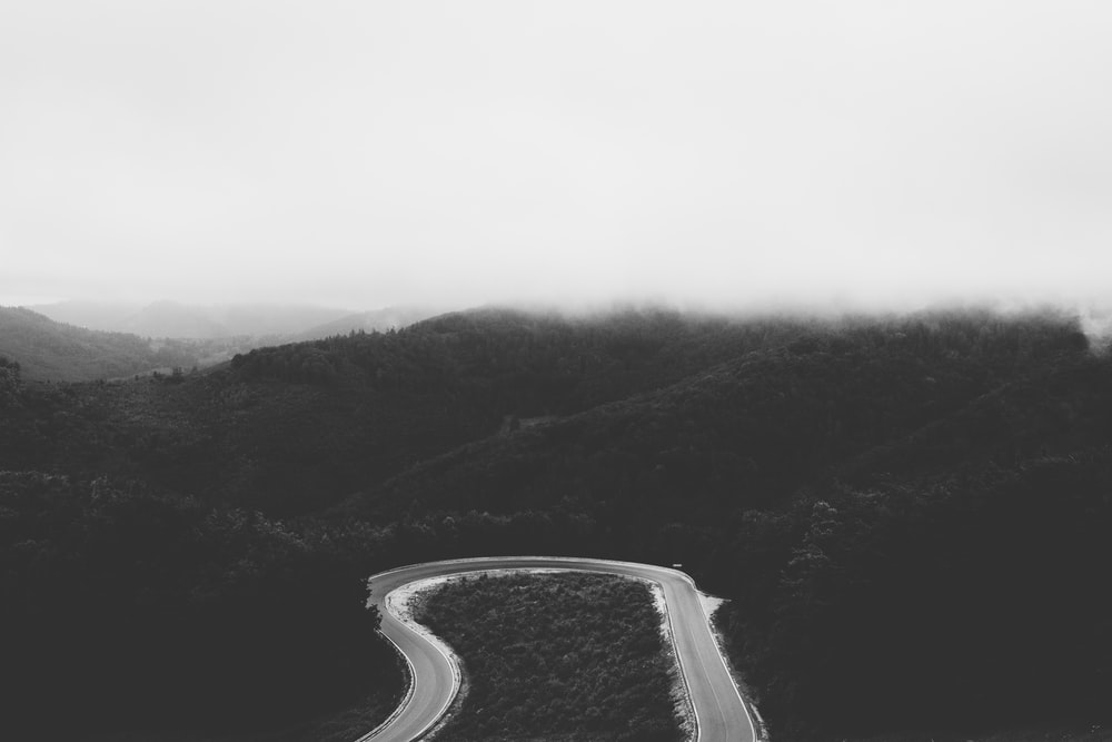 grayscale photo of road between mountains