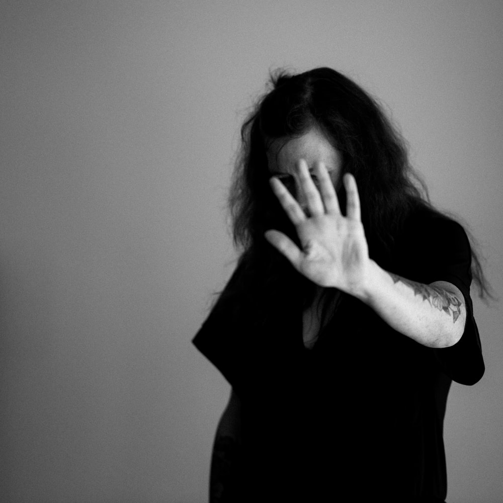 grayscale photo of woman covering her face with her hands