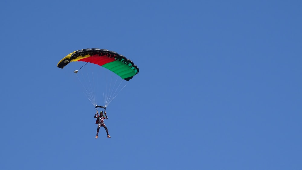 person in black jacket and blue denim jeans riding yellow and red parachute