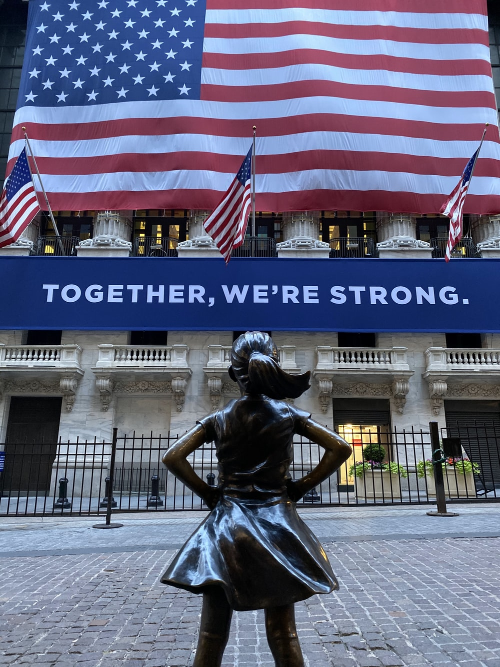 woman in black dress statue near american flag during daytime