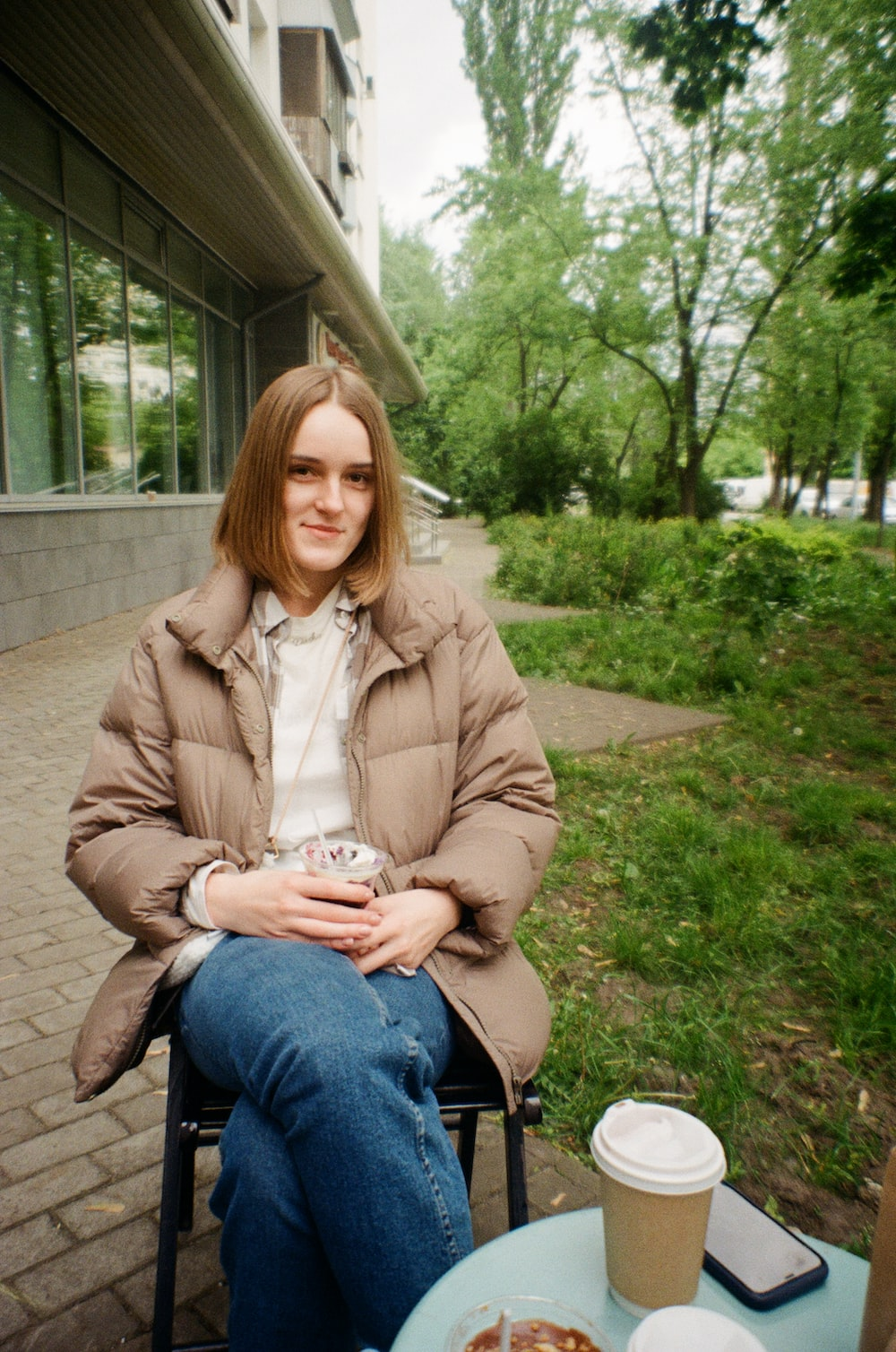 woman in brown coat sitting on green grass field during daytime