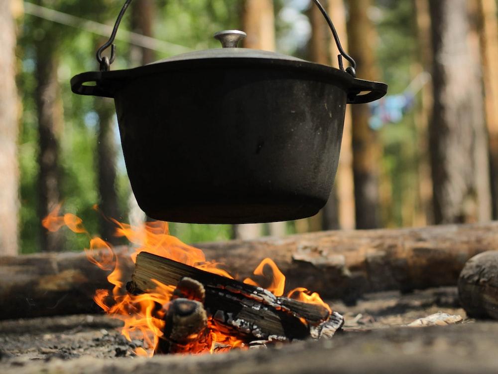 black cooking pot on burning wood