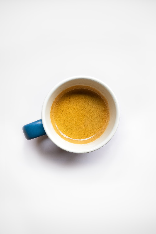 blue ceramic mug with brown liquid