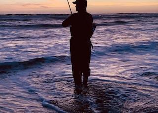 silhouette of man fishing during sunset