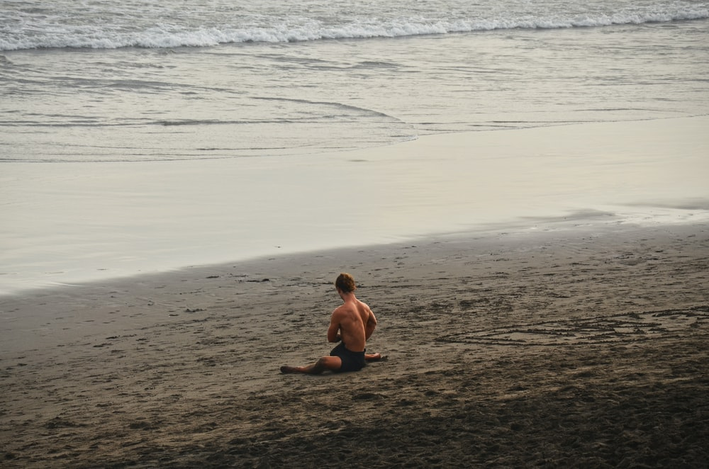topless boy sitting on beach during daytime