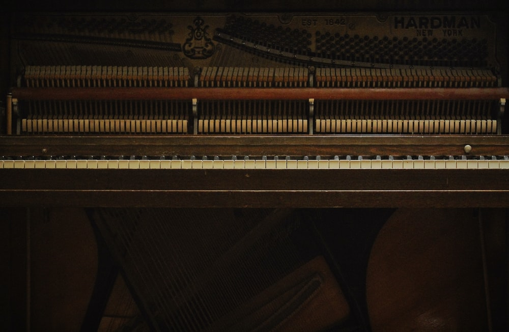 brown wooden upright piano with bench