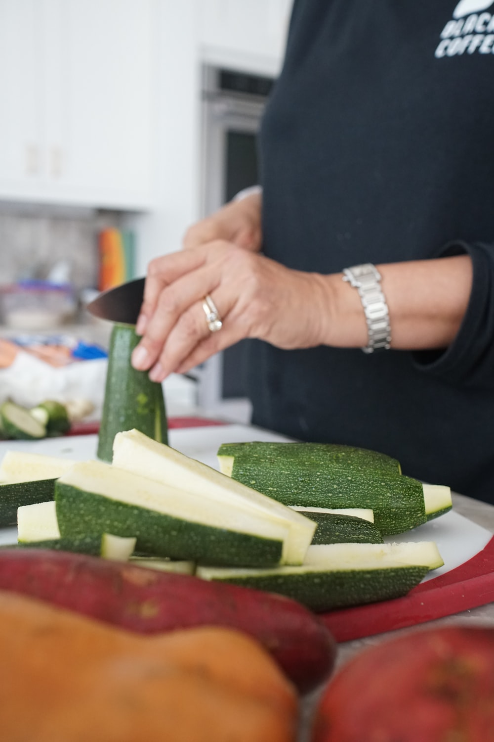 person holding sliced cucumber on brown wooden chopping board, avocado salsa