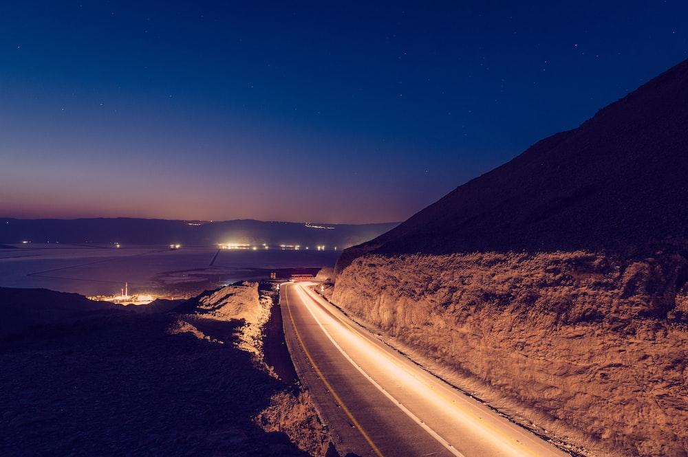black asphalt road near brown mountain during night time