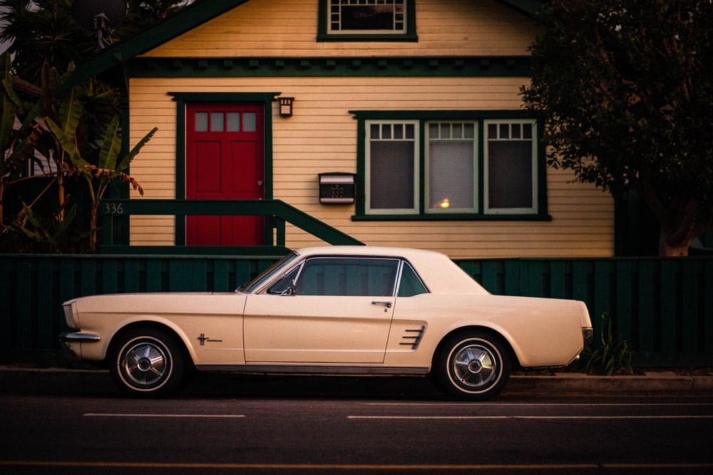 white coupe parked in front of white and red house