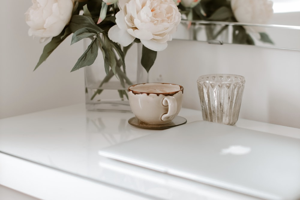 white flower on brown ceramic cup on white table