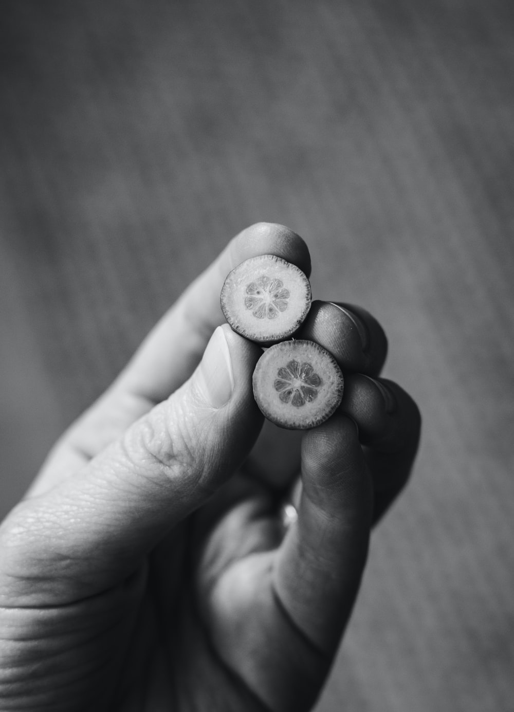 grayscale photo of person holding round coin