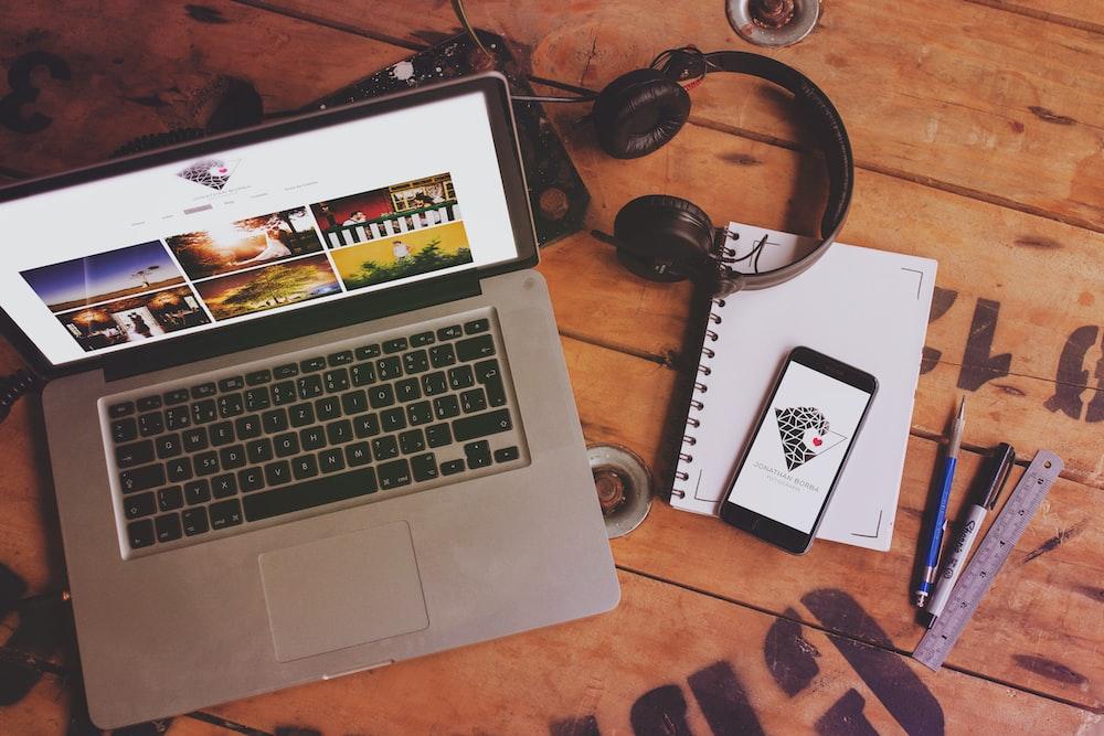 macbook pro beside black headphones and black headphones