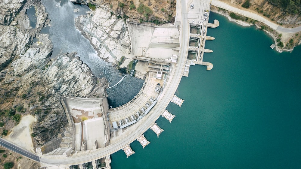 aerial view of white concrete building near body of water during daytime