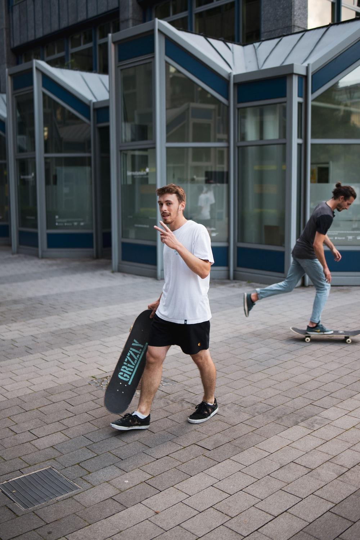 man in white t-shirt and black shorts playing skateboard during daytime