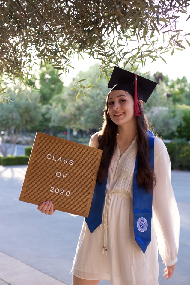 woman in blue academic gown holding brown wooden board