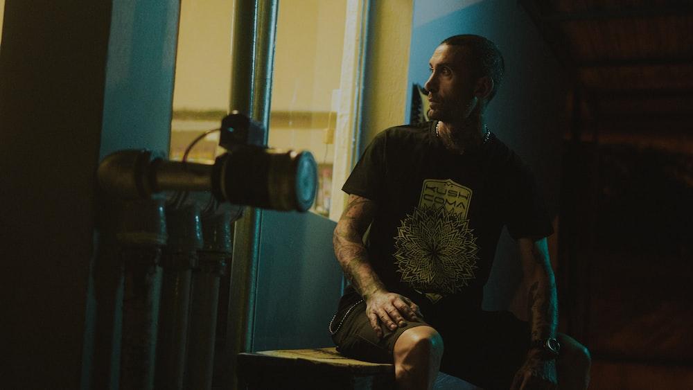 man in black crew neck t-shirt sitting on chair