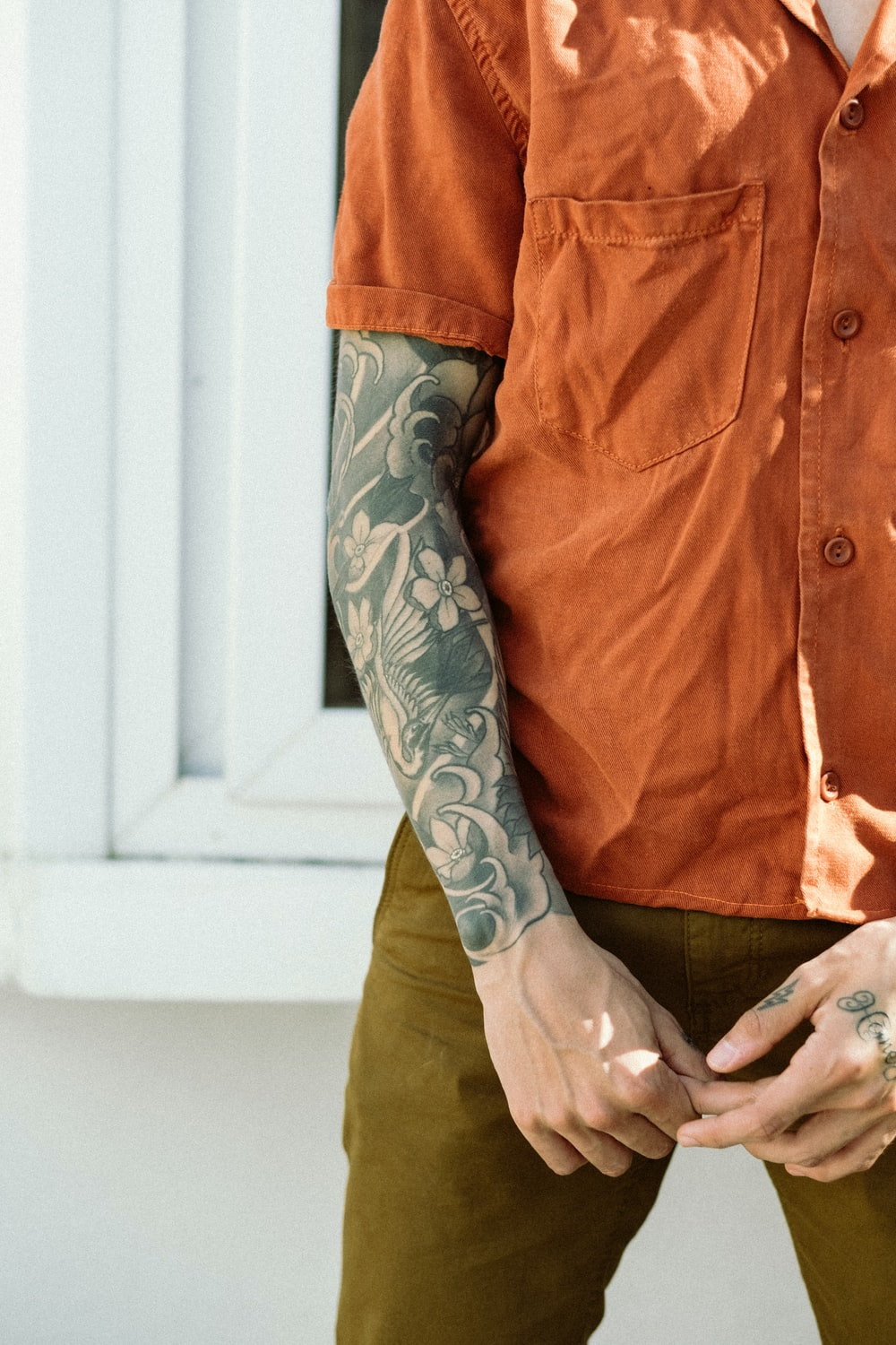 man in orange button up shirt with black and gray arm tattoo