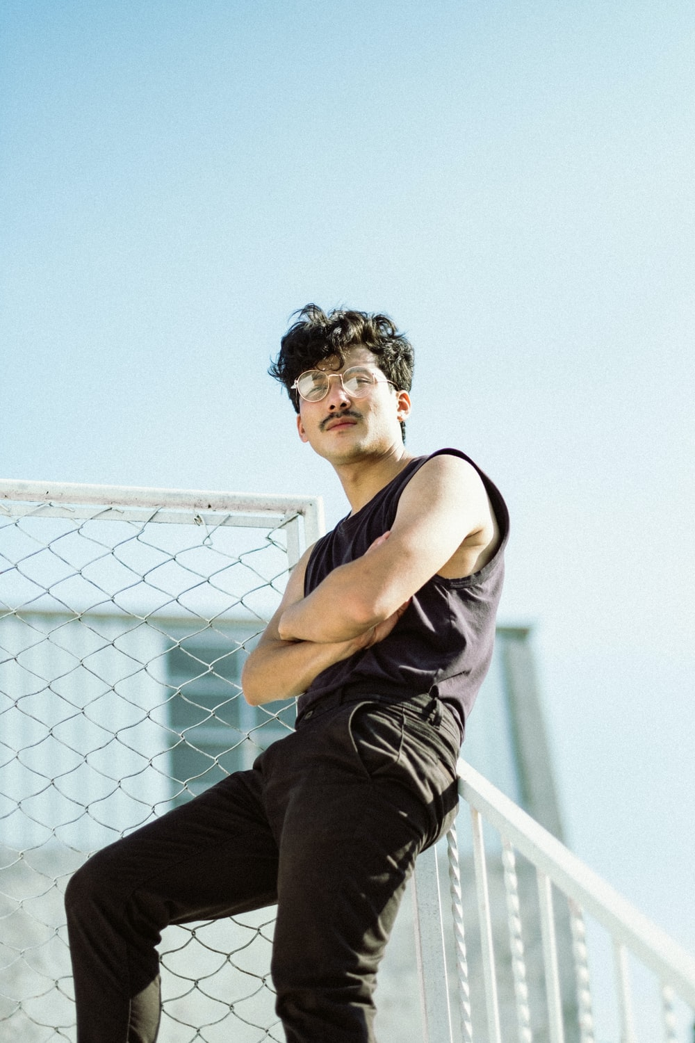man in black tank top and black pants sitting on white metal fence