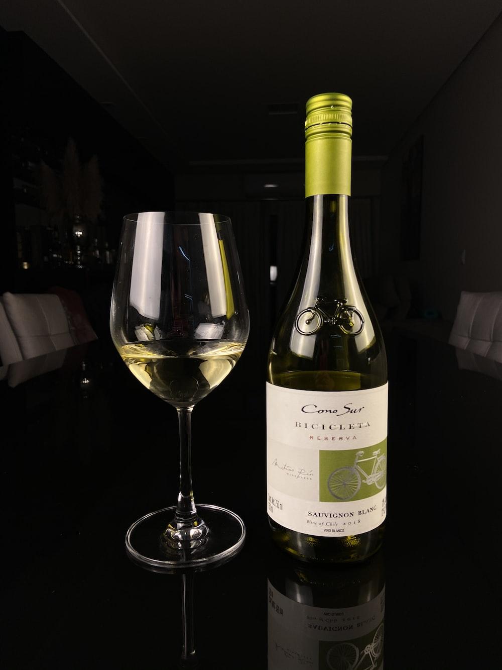 white labeled bottle beside wine glass