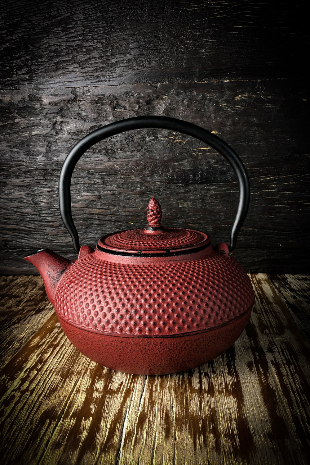 red ceramic teapot on brown wooden table