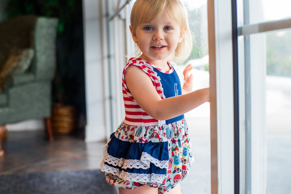 girl in red and white striped tank top and floral skirt standing beside glass window during