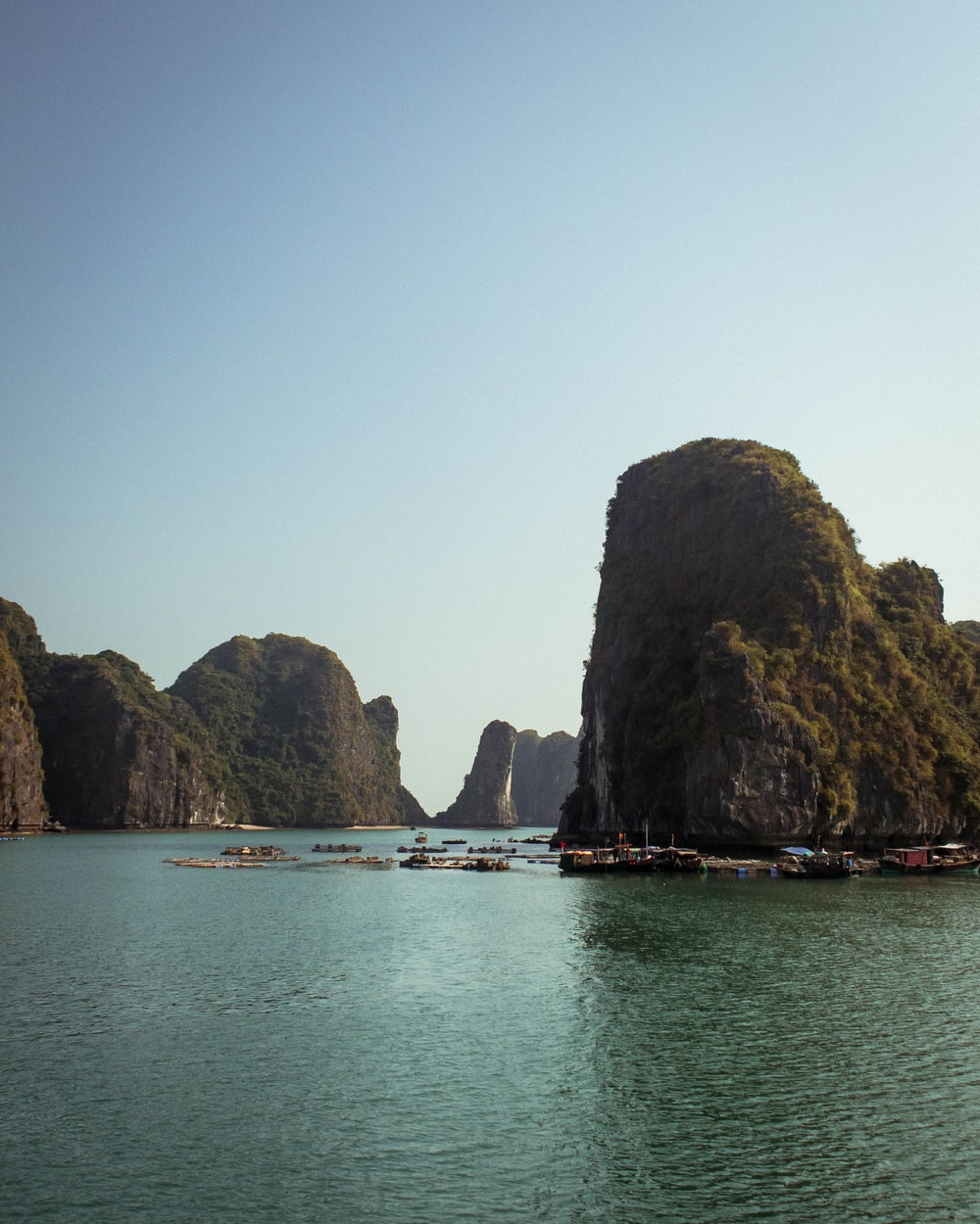 boats on sea near rock formation during daytime