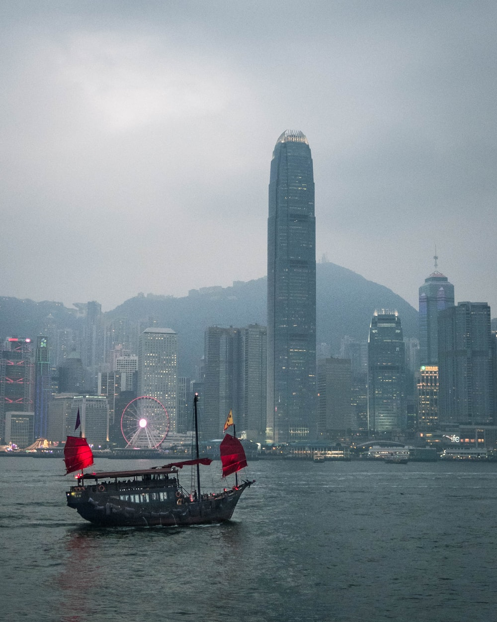 people riding on boat on water near city buildings during daytime
