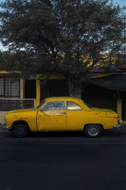 yellow sedan parked near brown tree