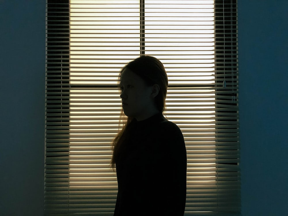 woman in black long sleeve shirt standing beside window blinds