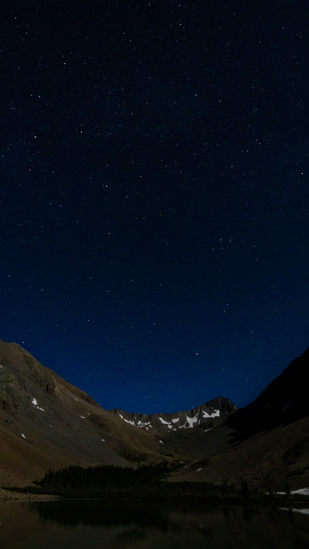 brown and green mountains under blue sky during night time