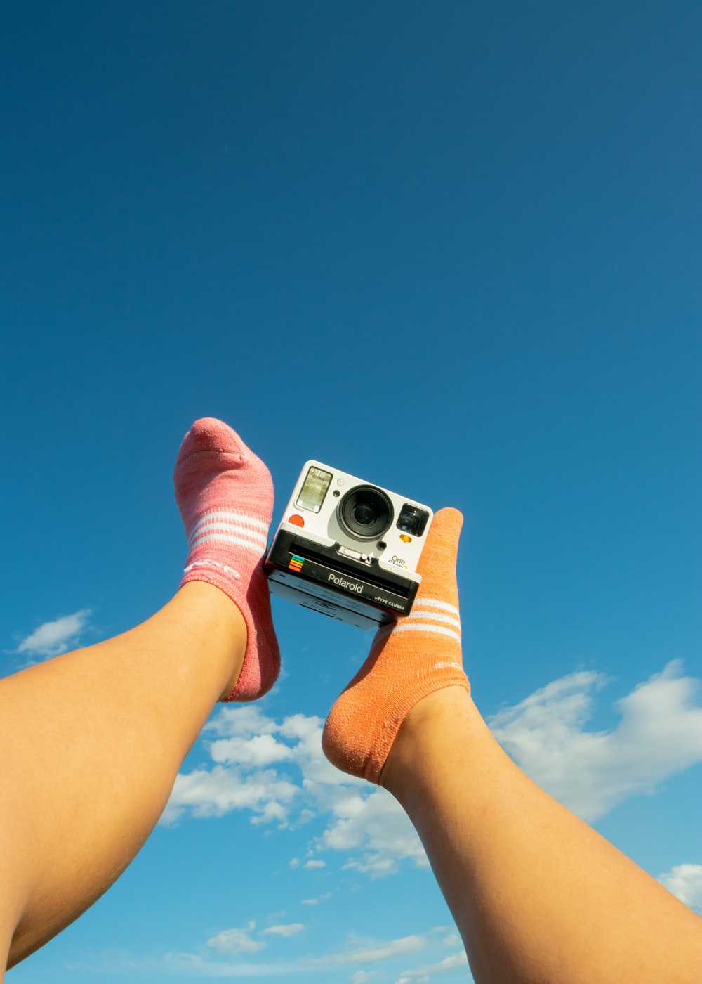 person holding white and black camera under blue sky during daytime
