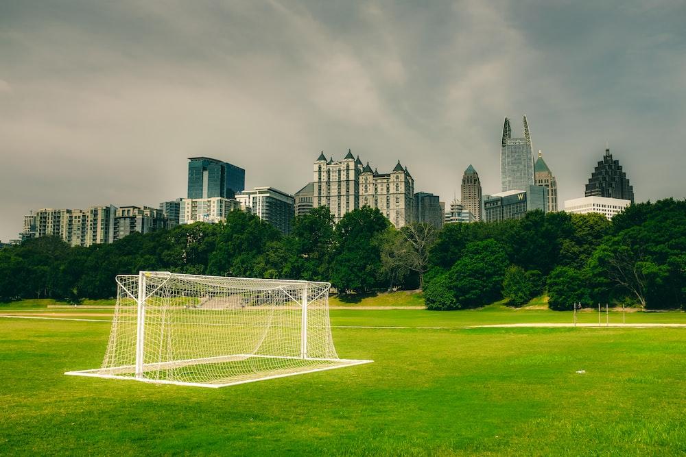 white soccer goal net on green grass field near city buildings during daytime