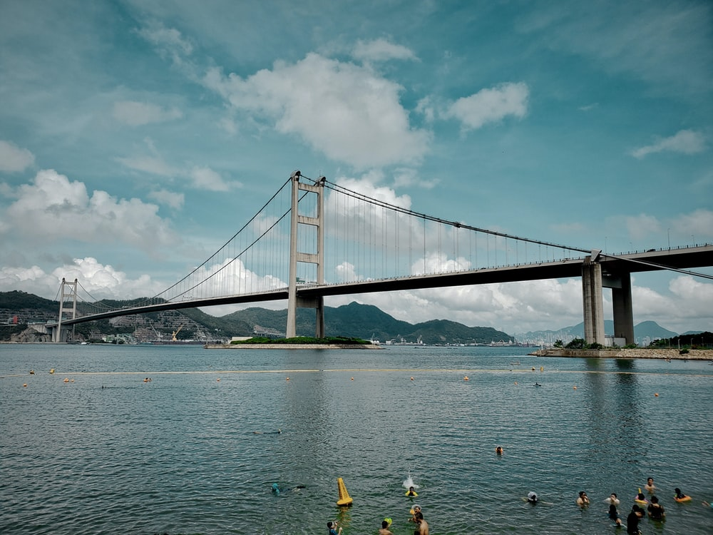 people riding on yellow kayak on sea near bridge under white clouds and blue sky during