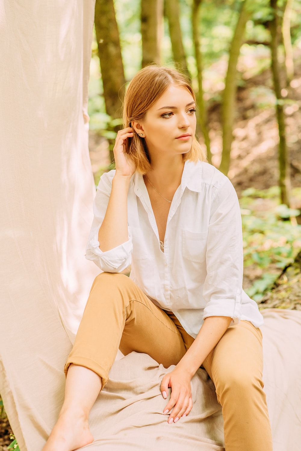 woman in white dress shirt sitting on brown wooden bench