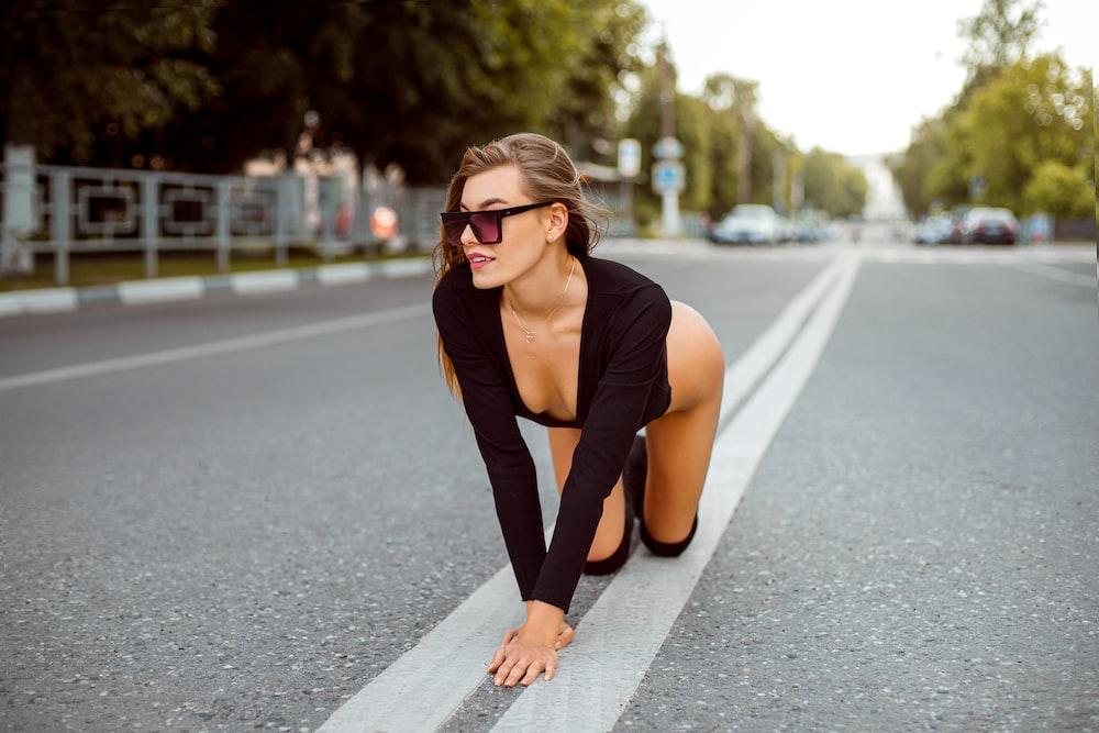woman in black tank top and black leggings wearing black sunglasses sitting on road during daytime