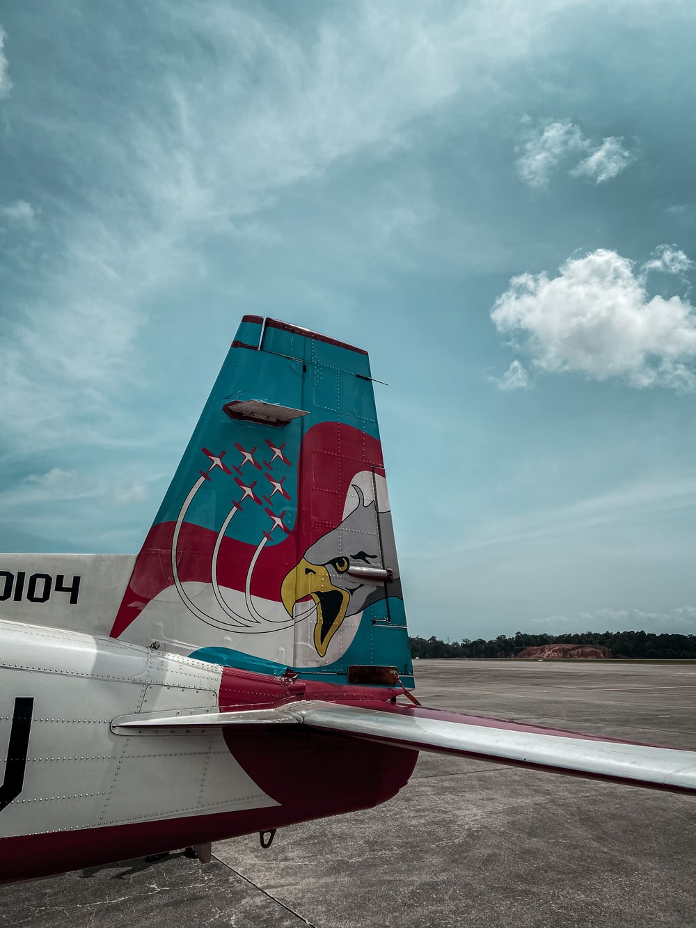 red and white airplane under white clouds and blue sky during daytime