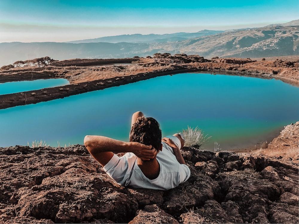 woman in white shirt sitting on brown rock near lake during daytime