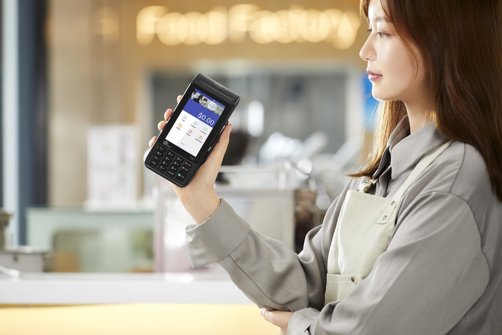 woman in gray coat holding black smartphone